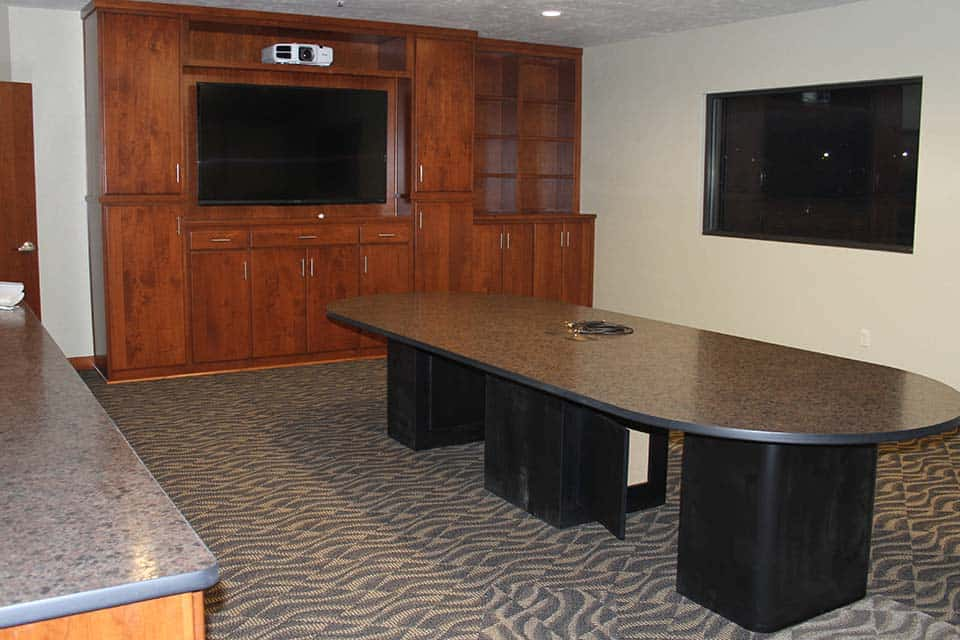 Conference room with large table in the middle, large cabinets with TV mounted in the middle and a large projector on top