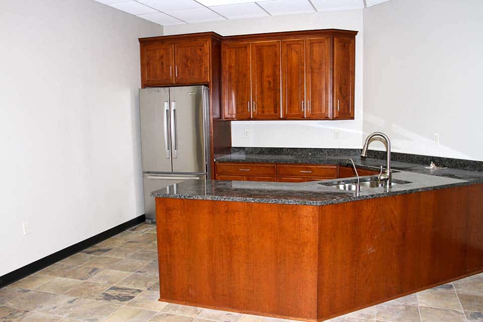 Kitchen with dark wood cabinets and granite counter tops in the Clean Water building by Fox Structures