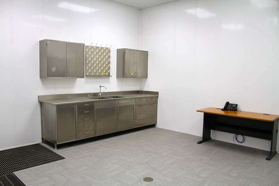 Testing station with stainless steel sink and cabinets with office table and phone on the right
