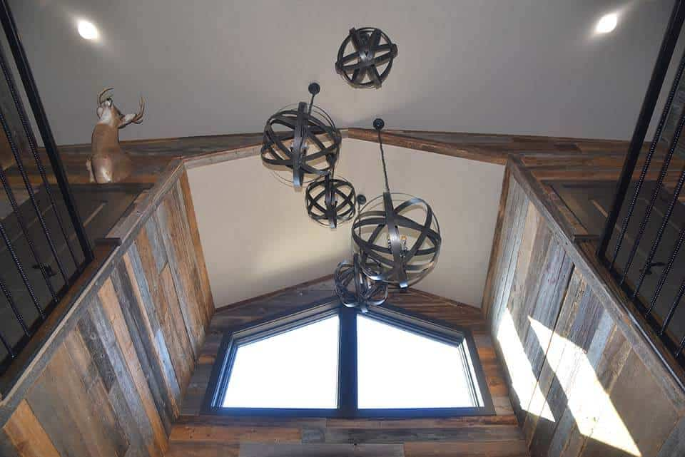 5 metal hanging lights and big windows above the entryway of the Forest Brook Farms building by Fox Structures