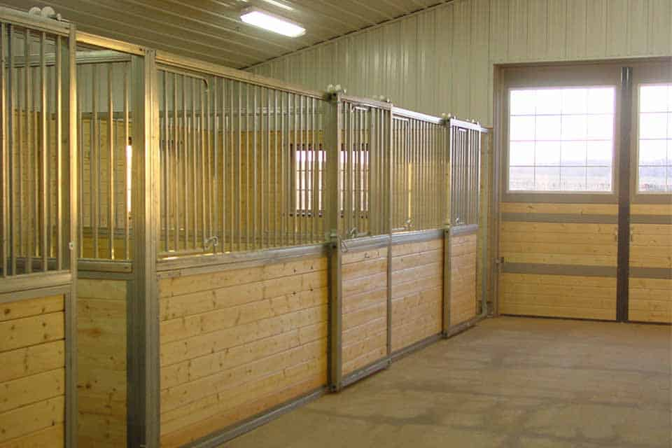 Equestrian Construction in Freedom, WI, custom built horse stalls with wooden paneling on bottom and custom built stainless steel railings at the top