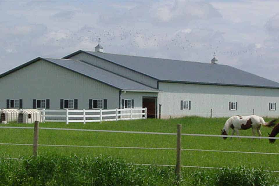 Equestrian construction in Kaukauna, WI. Equestrian storage facility with horses grazing out in front pasture